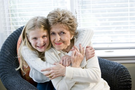 Portrait of happy young girl hugging grandmother at home photo