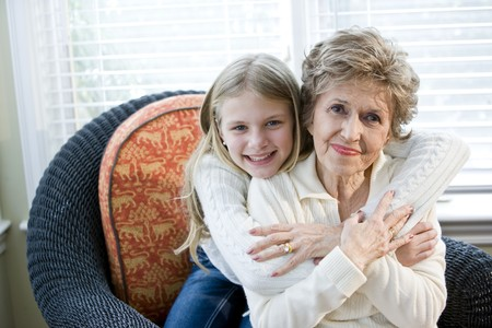 Portrait of happy young girl hugging grandmother at home Stock Photo - 7181842