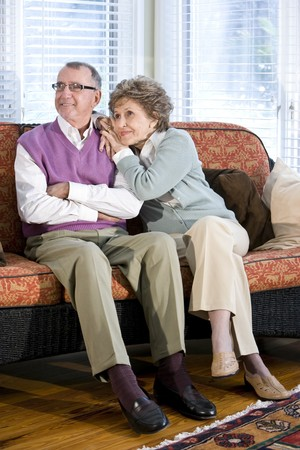 Happy senior couple sitting together on couch in living room photo