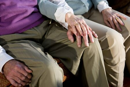 affection: Hands of affectionate elderly couple touching on knee