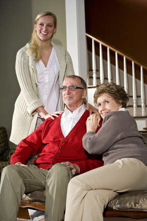 Senior couple on couch at home with adult daughter photo