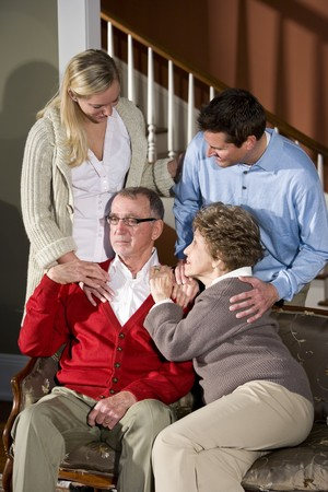 Senior couple on couch at home with adult children photo