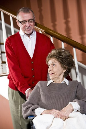 Smiling senior couple at home, woman in wheelchair photo