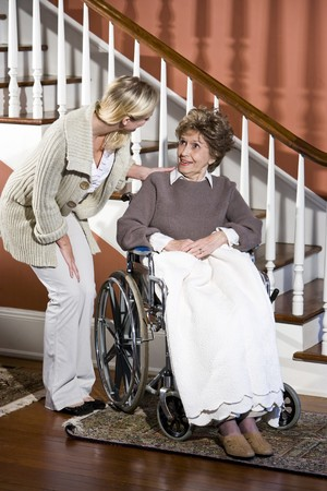 helping people: Senior woman in wheelchair with nurse helping Stock Photo