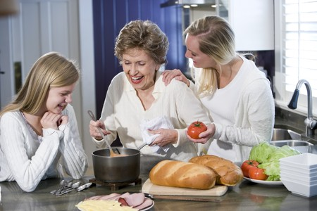 three generations of women: Grandmother with family cooking in kitchen, smiling and laughing together