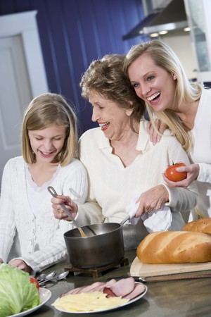 Grandmother with family cooking in kitchen, smiling and laughing together Stock Photo - 7181760