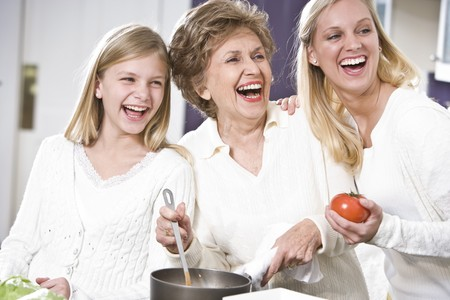 grandmother grandchild: Grandmother with family cooking in kitchen, smiling and laughing together