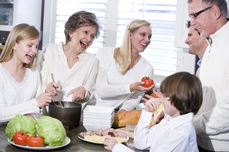 three generation: Grandmother with family cooking in kitchen, smiling and laughing together