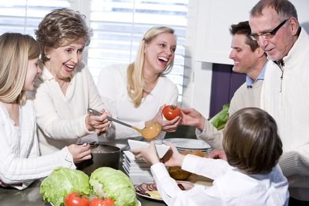 padres hablando con hijos: Abuela con familia cocinar en cocina, sonriendo y re�r juntos  Foto de archivo