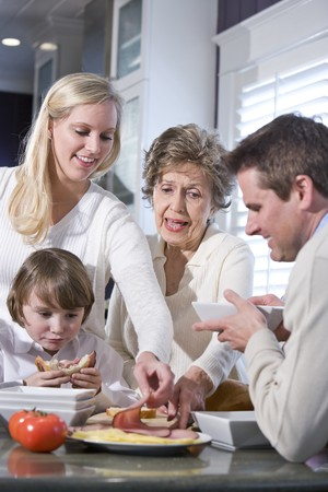 three generation: Grandmother with family eating lunch in kitchen Stock Photo