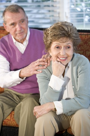 Happy senior couple sitting together on sofa, focus on woman photo