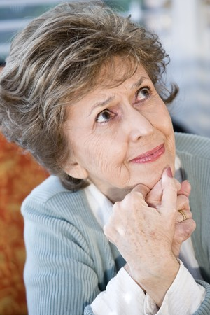 Face of elderly woman looking up with serious expression photo