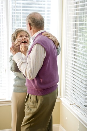 Happy senior couple dancing together in living room Stock Photo - 7181747
