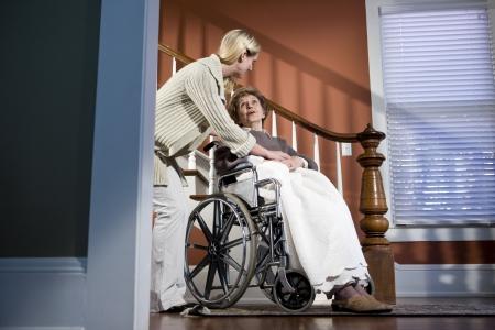 ni�os ayudando: Mujer de edad avanzada de la helding de enfermera femenino en silla de ruedas en el hogar Foto de archivo