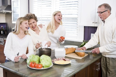three generation: Multi-generational family making lunch in kitchen, laughing and talking