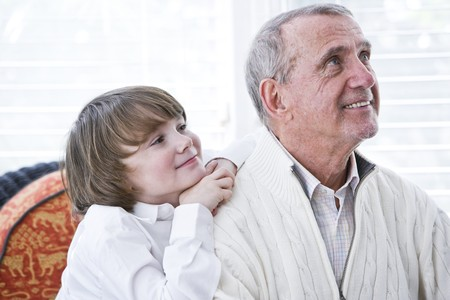 Happy young boy leaning on shoulder of grandfather looking up photo