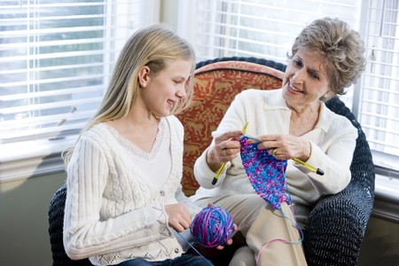art and craft: Grandmother teaching granddaughter how to knit Stock Photo