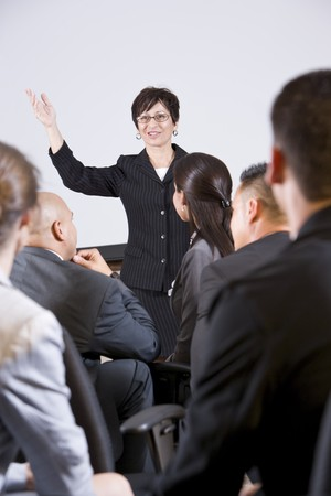 woman speaking: Hispanic woman standing in front, speaking to group of business people