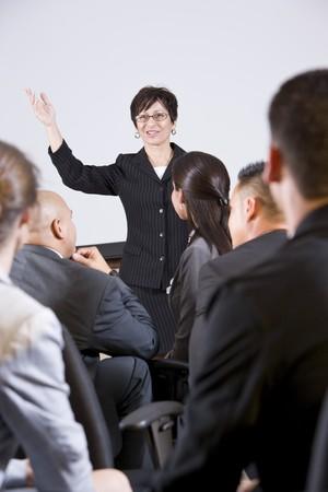 talking businessman: Mujer hispana pie delante, hablando a un grupo de personas de negocios