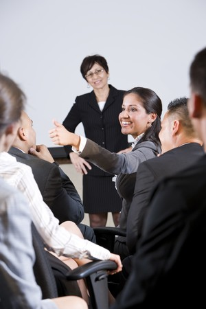 Group of businesspeople, focus on woman in audience speaking photo