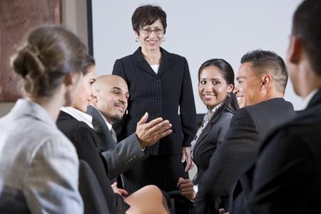 lead: Gruppo eterogeneo di businesspeople conversa con la donna in piedi di fronte alla