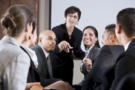 lead: Diverse group of businesspeople conversing with woman standing at front