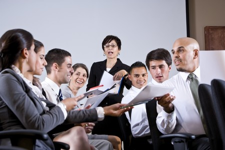 handouts: Hispanic woman leading diverse group of young business people in training seminar Stock Photo