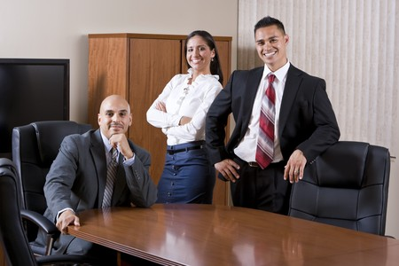 Three Hispanic business people smiling in boardroom photo