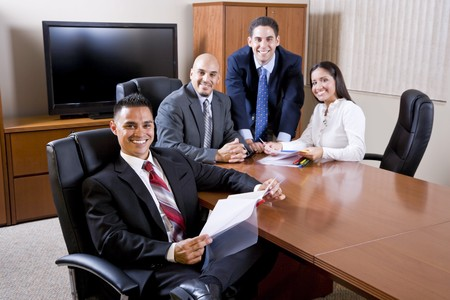 Hispanic business people meeting in boardroom, focus on man in foreground photo