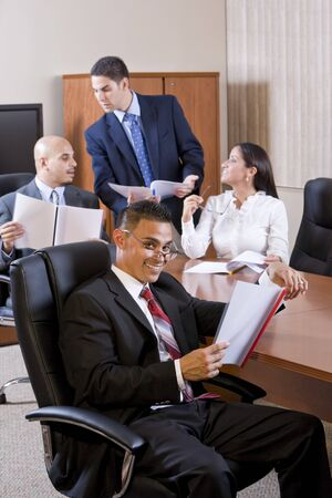 Hispanic businessman in meeting reviewing report, colleagues discussing photo
