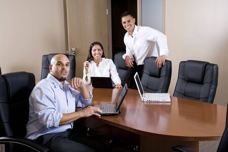 Mid-adult Hispanic office workers in boardroom meeting with laptops photo