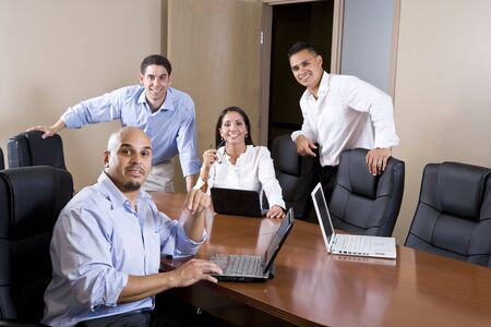 Mid-adult Hispanic office workers in boardroom meeting with laptops