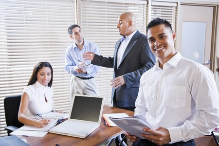 Hispanic business manager meeting with office workers, focus on man in foreground photo