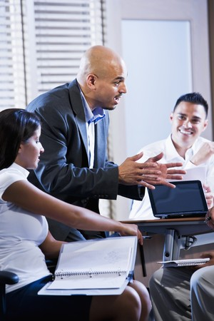 instructing: Hispanic business manager meeting with office workers, giving directions Stock Photo