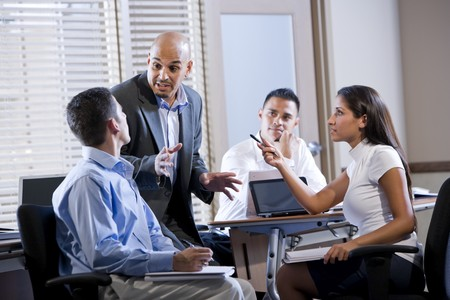 lead: Hispanic business manager meeting with office workers, giving directions Stock Photo