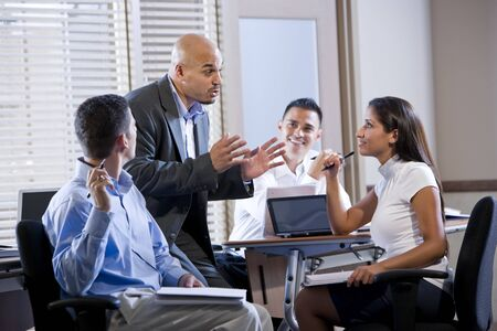 Hispanic business manager meeting with office workers, giving directions Banque d'images