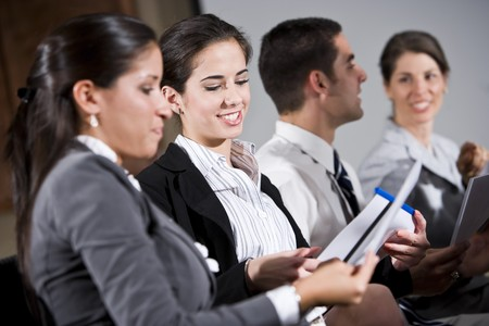 diverse group of people: Young business people or college students sitting in row reading report in presentation Stock Photo
