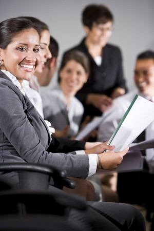 Young business people or college students sitting in row reading report in presentation photo