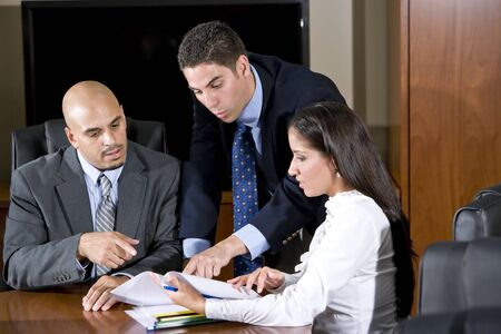 worried businessman: Three Hispanic office workers reviewing report Stock Photo