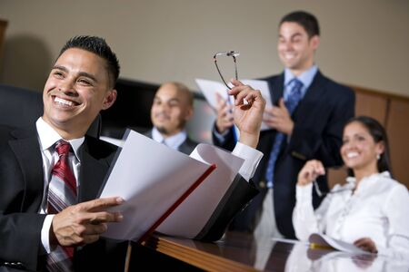 Hispanic business people in boardroom smiling watching presentation, focus on man in foreground photo