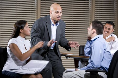Hispanic manager talking with group of office workers photo