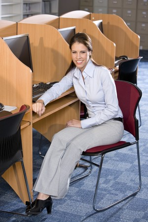 Female college student sitting at computer in library Stock Photo - 7159243