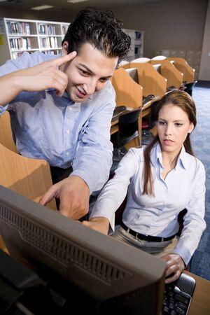 estudiantes universitarios: Dos estudiantes universitarios, utilizando equipo de biblioteca apuntando al monitor