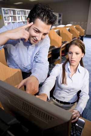 Two university students using computer in library pointing at monitor Stock Photo - 7159188