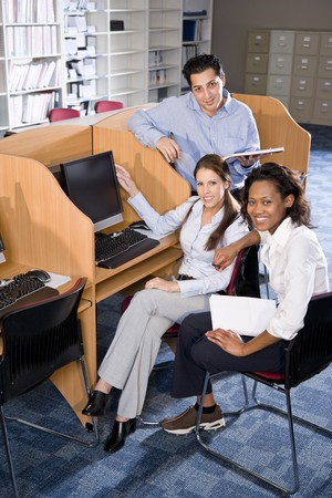 Diverse university students at library computer studying photo