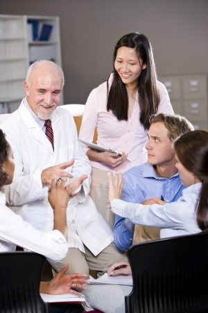 Professor wearing lab coat having discussion with college students Stock Photo - 7159174
