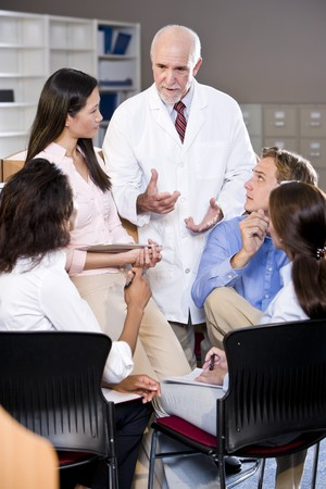 university professor: Professor wearing lab coat having discussion with college students