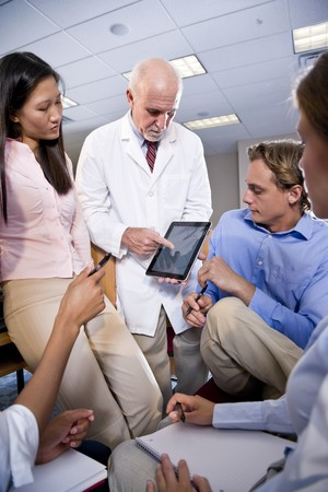 Professor wearing lab coat having discussion with college students photo