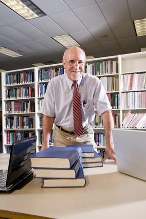 Portrait of mature man at library table with textbooks, professor researching