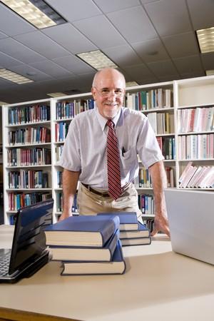 Retrato de un hombre maduro a la mesa de la biblioteca con libros de texto, profesor de investigación